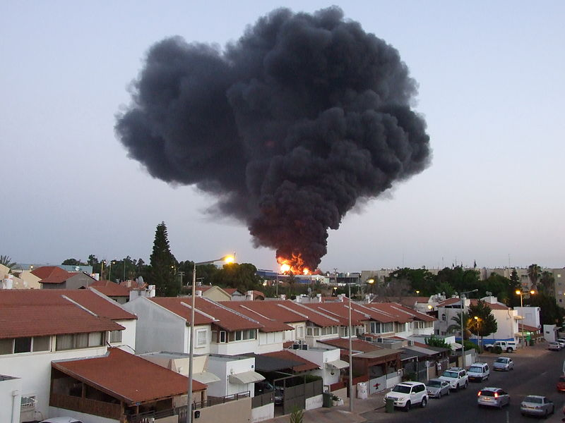 A burning factory in Sderot that was hit by a rocket from Gaza on June 28. Credit: Natan Flayer via Wikimedia Commons.