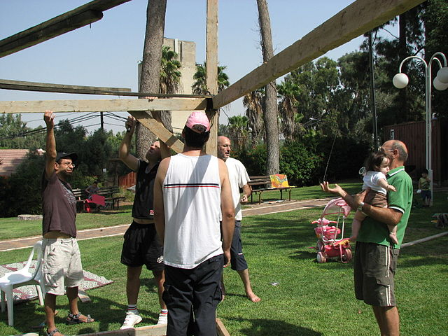 Click photo to download. Caption: The construction of a sukkah in Ramat Hacovesh, Israel. One possible advantage of renting a sukkah over owning one is avoiding the process of putting up and taking down the sukkah yourself. Credit: PikiWiki - Israel free image collection project.
