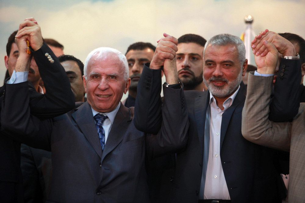 Click photo to download. Caption: Head of the Hamas government Ismail Haniyeh (right) and senior Fatah official Azzam Al-Ahmed (left) raise their hands together at a news conference that announced a unity agreement between the rival Palestinian factions in Gaza City on April 23, 2014. Credit: Abed Rahim Khatib/Flash90.
