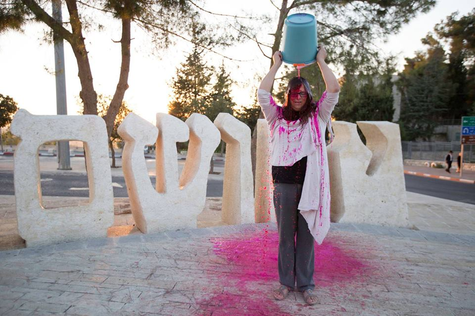 "A member of ""Jews Against Genocide"" performs a ""Blood Bucket Challenge in front of Israel's Yad Vashem Holocaust memorial. Credit: Facebook."
