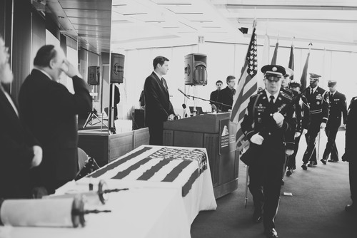 Click photo to download. Caption: The color guard marches during an Oct. 12 dedication of a Torah scroll for the U.S. military at the Museum of Jewish Heritage in Manhattan. At the podium is Jacob Kamaras, and at left giving a salute is his father, Philip Kamaras. Credit: Alexa Drew Photography.