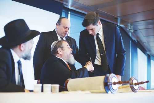 Click photo to download. Caption: On Oct. 12 at the Museum of Jewish Heritage in Manhattan, Jacob Kamaras (right) and scribe Zerach Greenfield complete the final letter in a new Torah scroll for the U.S. military. Behind Greenfield is an emotional Philip Kamaras, Jacob's father. At left is Rabbi Yisroel Reisman, leader of the Agudath Israel of Madison congregation. Credit: Alexa Drew Photography.