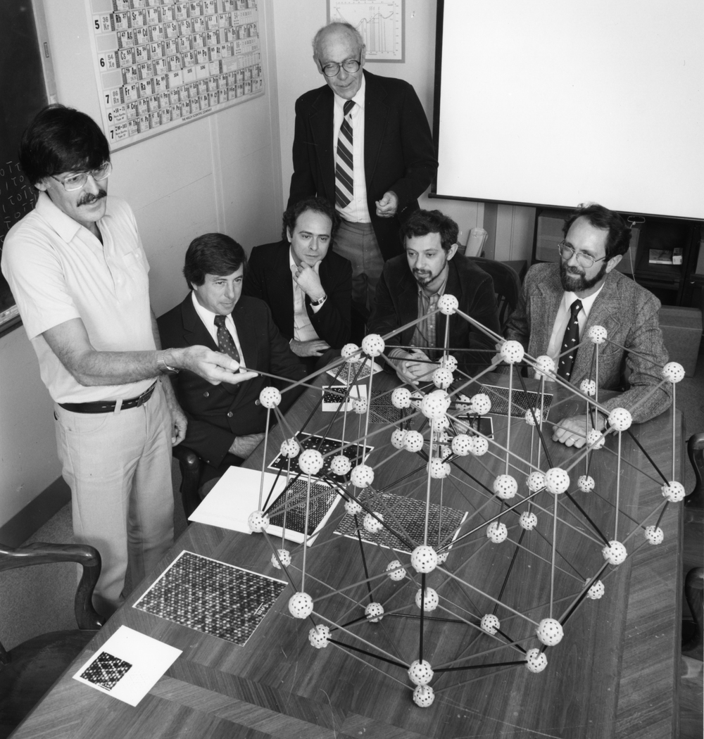 Click photo to download. Caption: Dan Shechtman (far left) discusses his groundbreaking discovery of quasicrystals with collaborators at the Maryland-based National Institute of Standards and Technology in 1985. Credit: Phillip Westcott, National Institute of Standards and Technology.