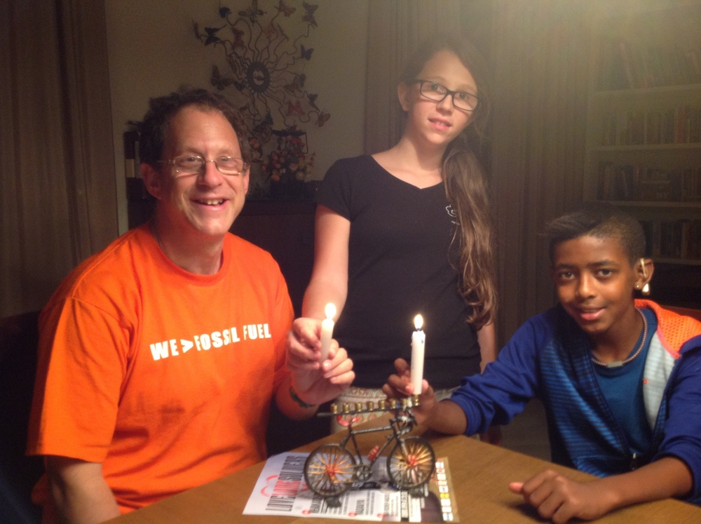 Click photo to download. Caption: Solar power pioneer Yosef Abramowitz (left) is pictured here with his children Ashira and Zamir as the family uses its bicycle-shaped Hanukkah menorah. Credit: Courtesy Yosef Abramowitz.