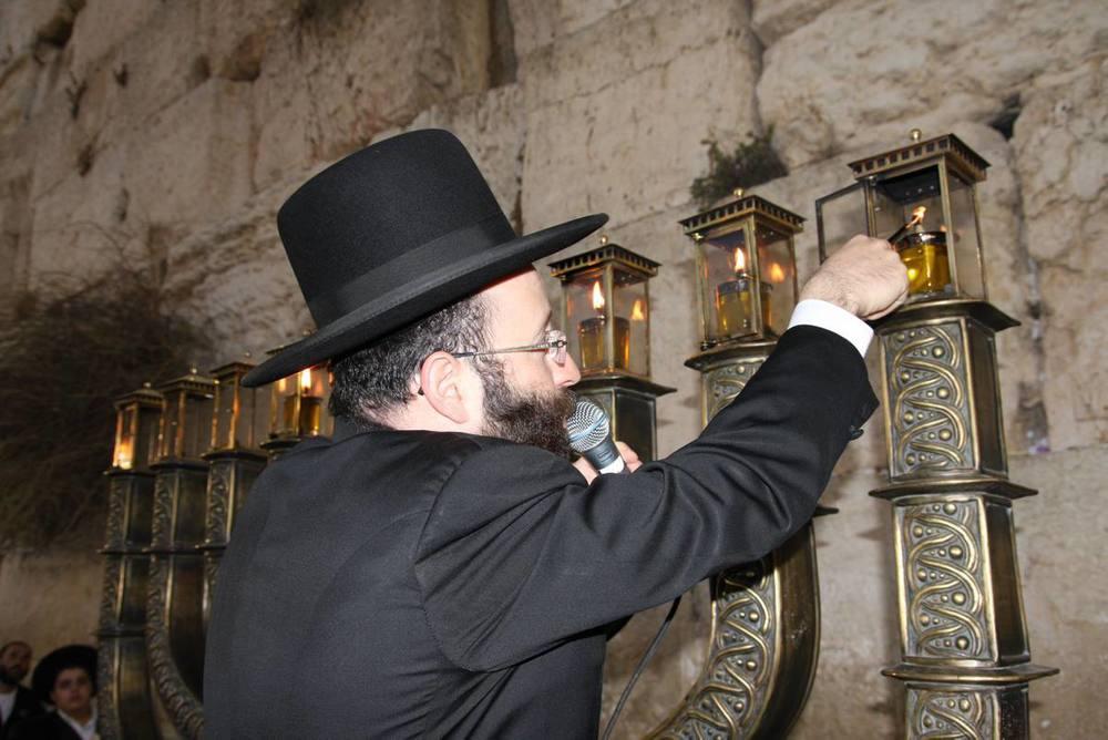 Click photo to download. Caption:Rabbi Shmuel Rabinowitz lights the Hanukkah menorah at the Western Wall. Credit: CourtesyRabbi Shmuel Rabinowitz.