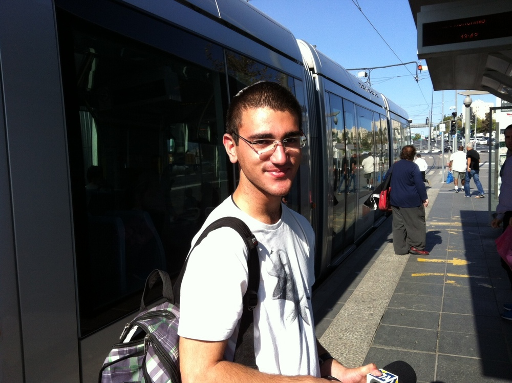 Click photo to download. Caption:  David Alcalay, 19, on the platform at the Ammunition Hill light rail station. Credit:   Deborah Fineblum Schabb.