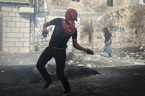 Click photo to download. Caption:On Oct. 30, 2014, a Palestinian rock thrower targets Israeli police in Jerusalem's Abu Tor neighborhood, near the house of the Palestinian man suspected of attempting to assassinate Temple Mount activist Yehudah Glick. Credit: Hadas Parush/Flash90.