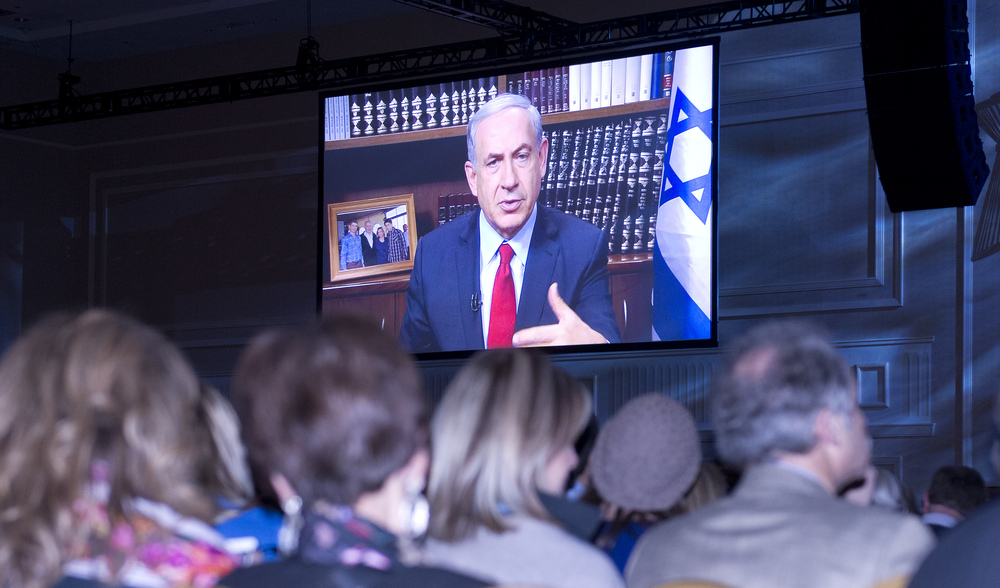 Prime Minister Benjamin Netanyahu addresses the Jewish Federations of North America General Assembly on Tuesday via a live video feed. Credit: Ron Sachs.