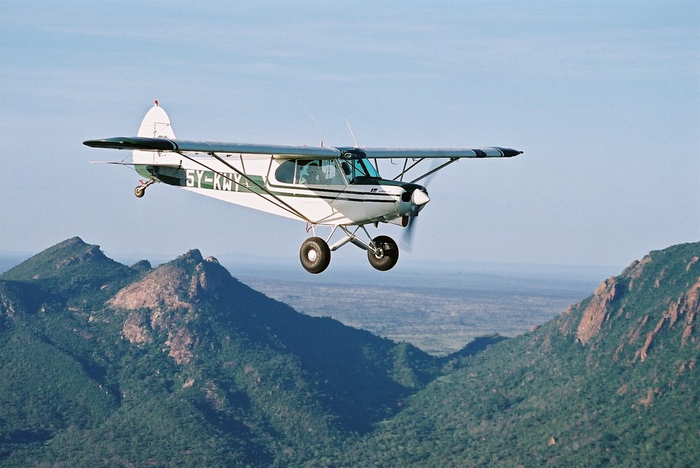 Click photo to download. Caption: A former Israeli Air Force plane, which was restored by Israeli volunteers at Herzliya Airport and then donated to the Kenya Wildlife Service for its fight against animal poaching, flies over the Ngulia Hills of Kenya's Tsavo West National Park. Credit: Courtesy Bill Clark.