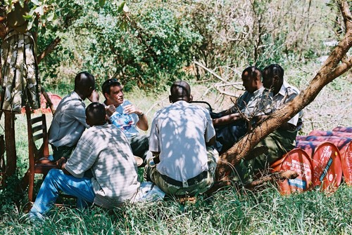 "Click photo to download. Caption: Zvi Ozer, an Israeli pilot and flight instructor who volunteers in Kenya, is pictured here teaching five Kenya Wildlife Service pilots in a ""bush classroom"" under an acacia tree at Kilaguni in Tsavo West National Park. Credit: Courtesy Bill Clark."