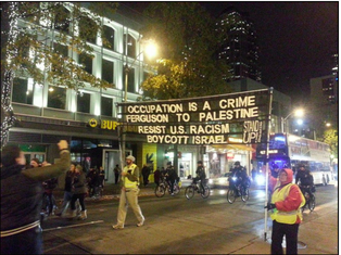 Pro-Palestinian activists holding a sign at a Ferguson protest in Seattle, WA. Credit: Screenshot from mikereport.wordpress.com.