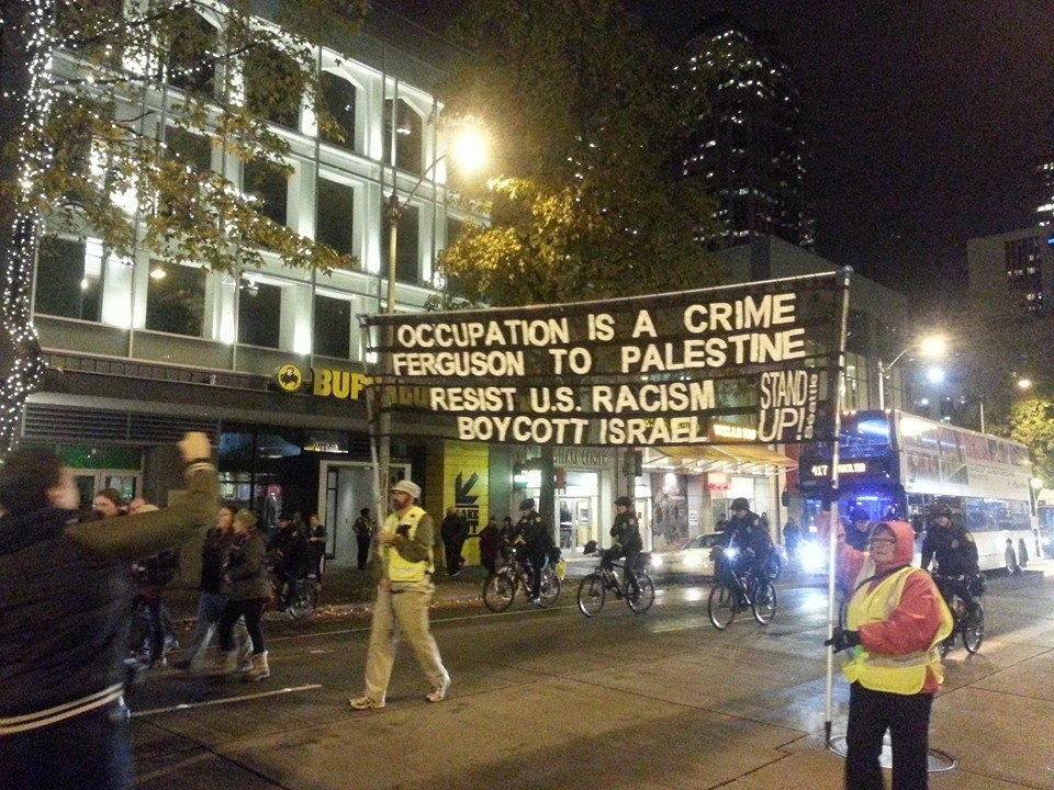 Click photo to download. Caption: In  a   protest against the Ferguson verdict o n Nov. 24 in Seattle, a sign uses the situation as a platform to promote a boycott of Israel. Credit: The Mike Report.