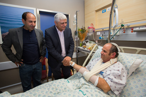 Click photo to download. Caption: Rami Levy and Ma'aleh Adumim Mayor Benny Kashriel visit Zohar Lomar, who was injured in the stabbing at the Rami Levy supermarket in the Mishor Adumim industrial zone at Hadassah Ein Kerem Hospital in Jerusalem on Dec. 4, 2014. Credit: Yonatan Sindel/Flash90.