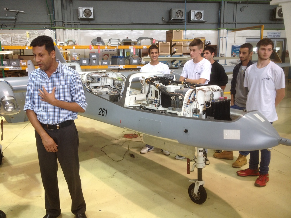 Click photo to download. Caption: Students of the industrial vocational high school based at Israel Aerospace Industries (IAI) stand next to a drone they are working on while their mentor, Gabi Daniels, addresses a visiting delegation from Friends of Israel Sci-Tech Schools, the U.S.-based group of supporters of the Israeli educational network to which the IAI high school belongs. Credit: Jacob Kamaras.