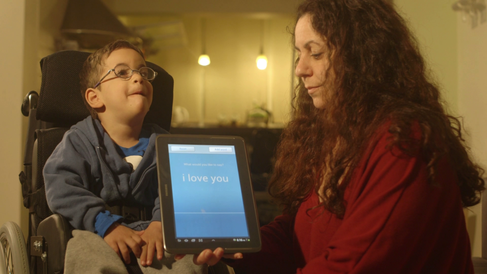 "Click photo to download. Caption: The Israeli-developed TalkITT software helps a boy with a speech impairment communicate ""I love you."" Credit: VoiceITT."