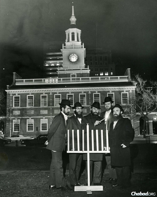 Click photo to download. Caption: Rabbi Abraham Shemtov, right, in front of Independence Hall in Philadelphia at the lighting of the first-ever public menorah in 1974. With him were yeshivah students who helped build the menorah from scratch. Credit: Lubavitcher Center/Chabad.org.
