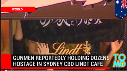 After taking hostages inside the Lindt cafe in central Sydney, Australia, the gunman forced the hostages to display an Islamist flag. Credit: YouTube screenshot.