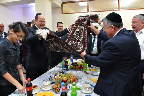 Israeli Minister of Defense Moshe Ya'alon (pictured at left, in center, holding rug) meets with representatives from the Jewish community in Baku, Azerbaijan's capital, on September 10, 2014. Credit: Ariel Hermoni/Ministry of Defense/Flash90.