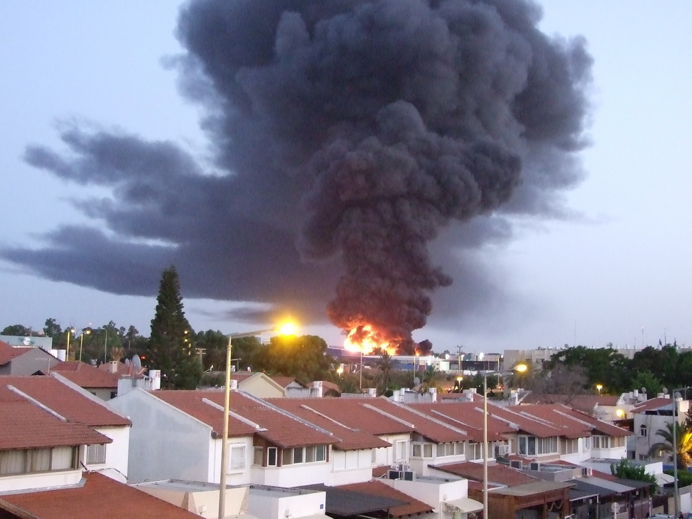 Click photo to download. Caption: A burning factory in the southern Israeli city of Sderot that was hit by a rocket fired from Hamas-controlled Gaza on June 28, 2014. Credit: Natan Flayer via Wikimedia Commons.