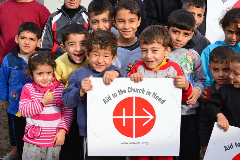 Click photo to download. Caption: Displaced Iraqi Christian children in Erbil, the largest city in Iraqi Kurdistan, hold a sign for the Catholic charity organization Aid to the Church in Need (ACN). Credit: ACN.