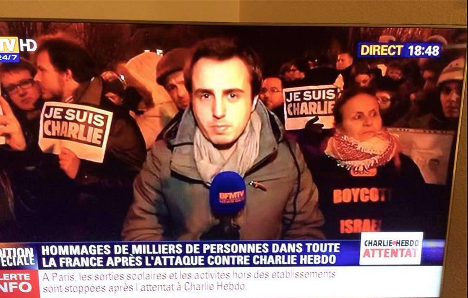 "Click photo to download. Caption: In this image circulating on social media depicts a news report from the scene of a mourners' rally for the murdered Charlie Hebdo journalists, a woman (pictured on the right) behind the reporter is seen wearing a shirt with the wording ""Boycott Israel,"" seemingly making the statement that Israel is somehow to blame for the attack on the magazine. Credit: Facebook."