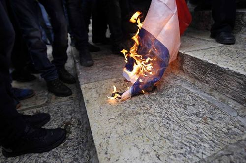 Palestinians burn the French flag on the Temple Mount on Friday in protest of the new cover of the French satirical magazine Charlie Hebdo. Credit: Facebook.