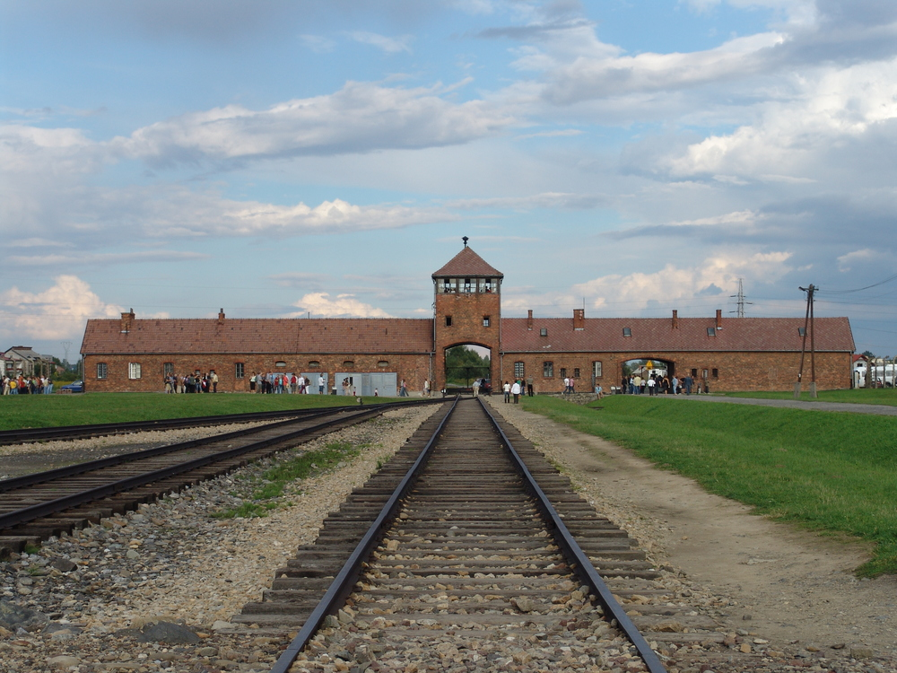 Click photo to download. Caption: The main gate at the former  Auschwitz II-Birkenau death camp. Credit: Angelo Celedon via Wikimedia Commons.