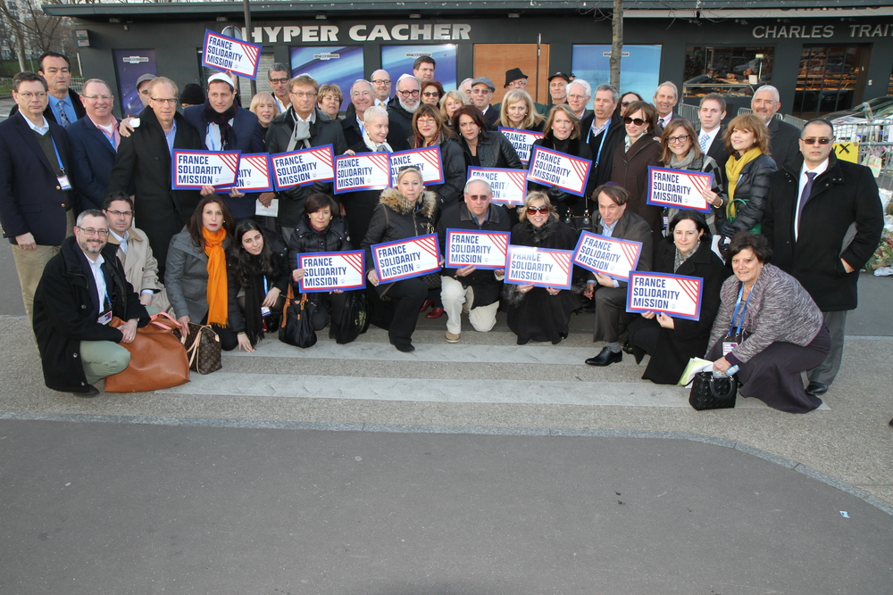 Click photo to download. Participants of the recent Jewish Federations of North America mission to Paris pose in front of the Hyper Cacher kosher grocery, where four Jewish shoppers were killed in an Islamist terror attack last month. Credit: The Jewish Federations of North America.