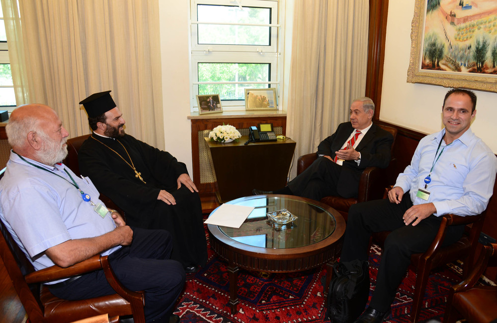 Click photo to download. Caption: On August 5, 2013, Israeli Prime Minister Benjamin Netanyahu (second from right) meets with Greek Orthodox priest Father Gabriel Nadaf (second from left) in Jerusalem. Pictured on the far right is Shadi Khalloul, who is now a candidate for the Knesset with Israeli Foreign Minister Avigdor Liberman's Yisrael Beiteinu party. Both Nadaf and Khalloul advocate for Christian enlistment in the Israel Defense Forces. Credit: Moshe Milner/GPO/Flash90.
