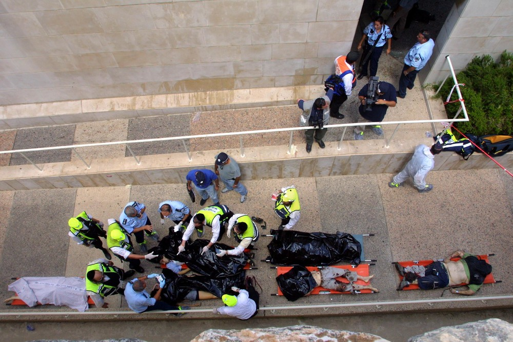 Click photo to download. Caption: Bodies are taken away following an explosion at the cafeteria of Jerusalem's Hebrew University on July 31, 2002. Hamas took responsibility for the bombing, which killed seven people and wounded 70, but a new U.S. federal court ruling found the Palestine Liberation Organization and the Palestinian Authority liable for that attack and other committed during the second intifada. Credit: Flash90.