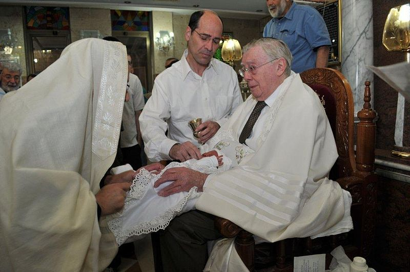 Some mohels who perform brit milah (pictured) use their mouths to remove blood from the infant in a practice known as metzitzah b'peh. Credit: Wikimedia Commons.
