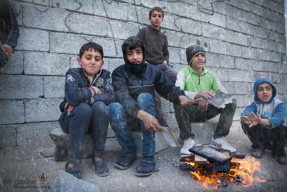 Click photo to download. Caption: Assyrian Christian children who were displaced by the Islamic State terror group are pictured in Ankawa, Iraq, trying to keep warm during a snowstorm. Credit: Jeff Gardner, Picture Christians Project, picturechristians.org.