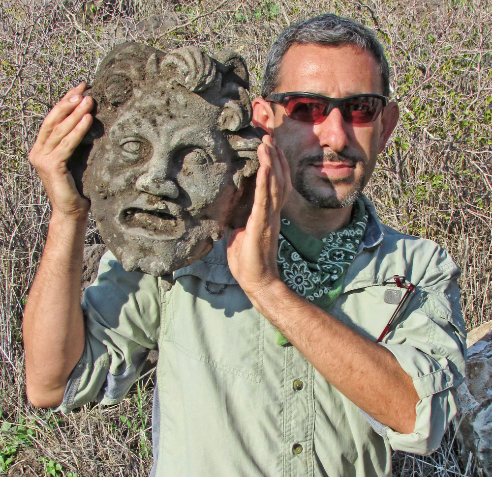 Researcher Dr. Michael Eisenberg of the Zinman Institute of Archaeology with the recently unearthed mask of the Greek god Pan. Credit: University of Haifa.