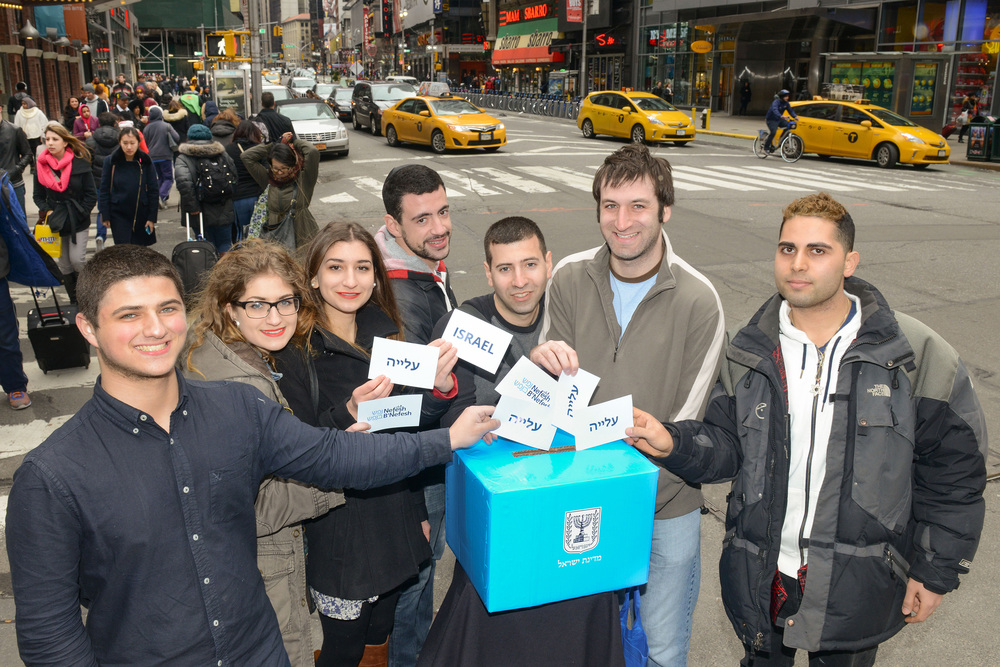 "Click photo to download. Caption: Pictured in New York City's Times Square, participants of the Nefesh B'Nefesh mega event in March ""vote"" for aliyah. From left to right: Yossi Cohen of Los Angeles, Rosalie Soussan of New York, Abby Soussan of New York, Jesse Bass of New York, Saul Daiell of New York, Michael Brenner of New York, and Yaakov Hatanian of New York. Credit: Shahar Azran, courtesy of Nefesh B'Nefesh."