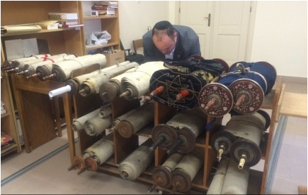 Jonny Daniels, founder and chairman of an Israel-based Holocaust commemoration organization called From The Depths, with 35 Torah scrolls that were recently discovered in a Polish monastery. Credit: Israel Hayom.