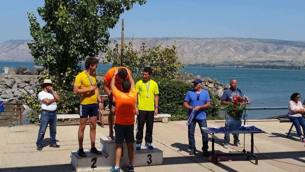 Click photo to download. Caption: With the Sea of Galilee in the background, Ilya Podpolnyy receives a gold medal at the 2015 Israeli kayaking championship. Credit: Orit Arfa.