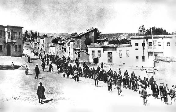 Armenian civilians, escorted by armed Ottoman soldiers, are marched through Harput (Kharpert) to a prison in the nearby Mezireh (present-day Elâzığ) in April 1915. Credit: Wikimedia Commons.
