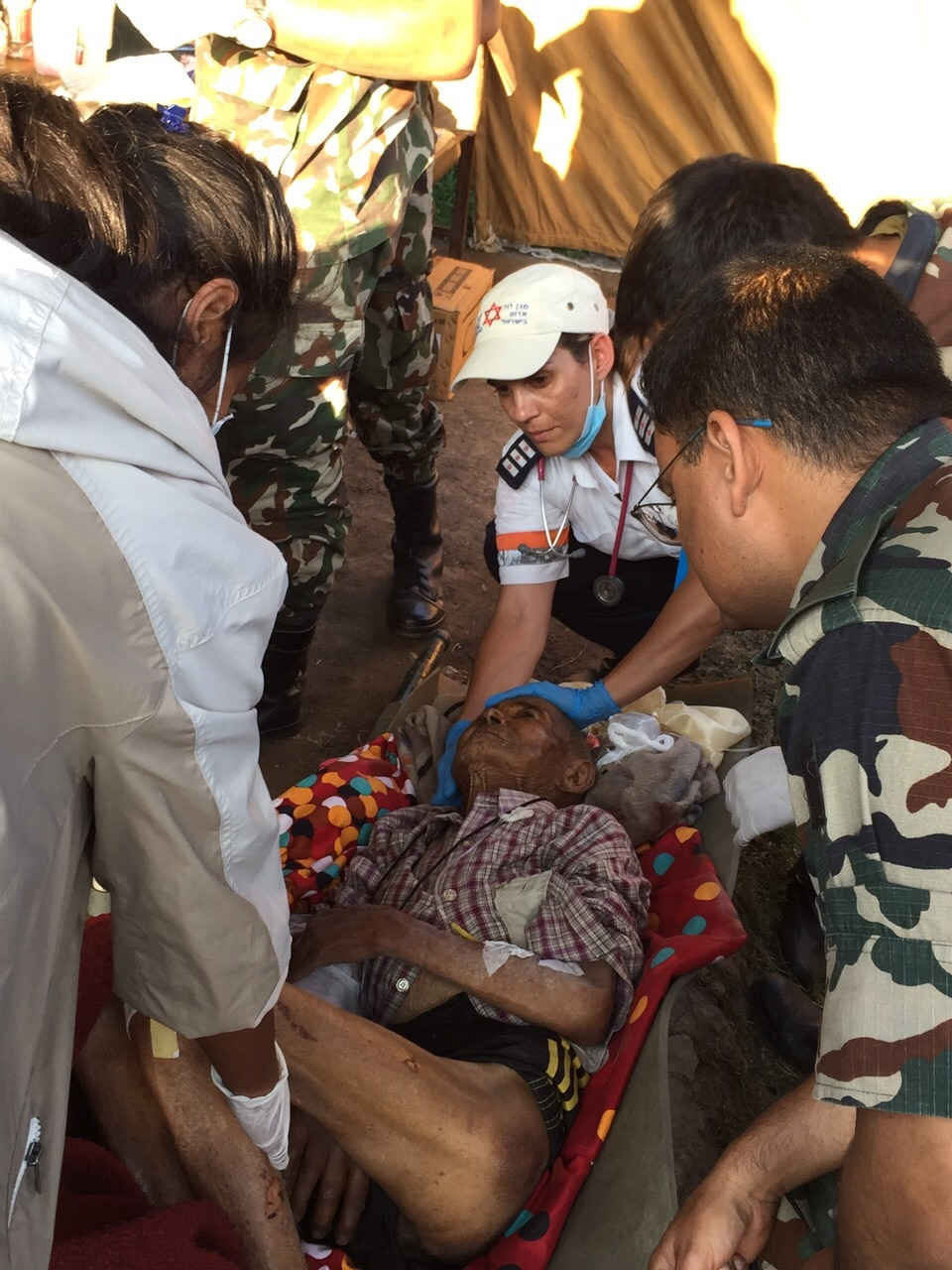 Click photo to download. Caption: Magen David Adom's Ravit Martinez (in center, wearing baseball cap) helps treat a wounded Nepalese citizen at a military hospital following the deadly earthquake that struck Nepal. Credit: Magen David Adom.