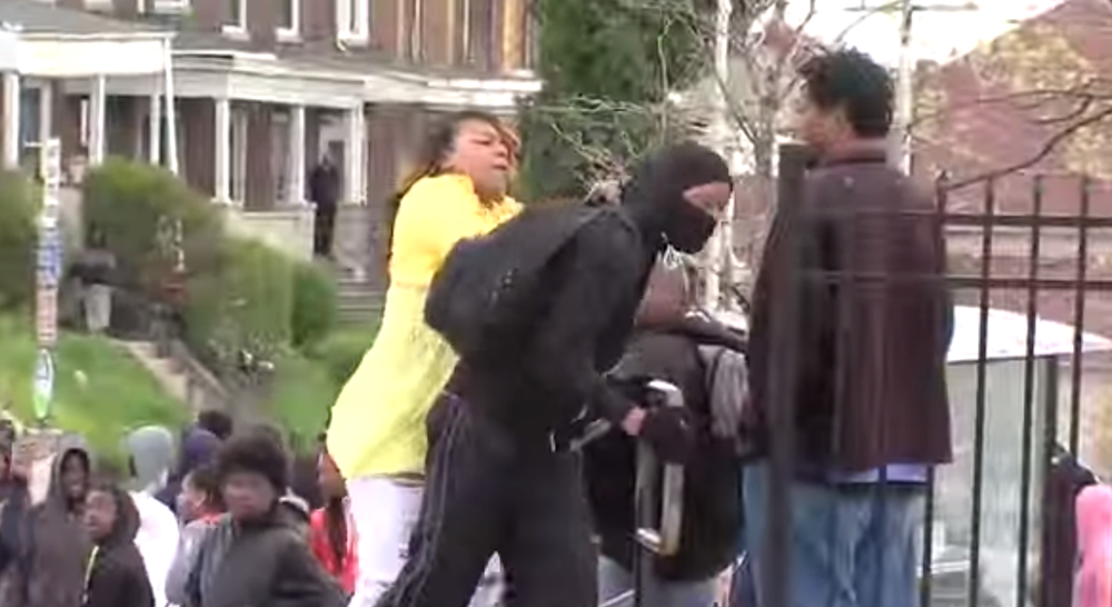 "Click photo to download. Caption: Toya Graham, dubbed ""the Baltimore Riot Mom,"" slaps her rioting son. Credit: YouTube."