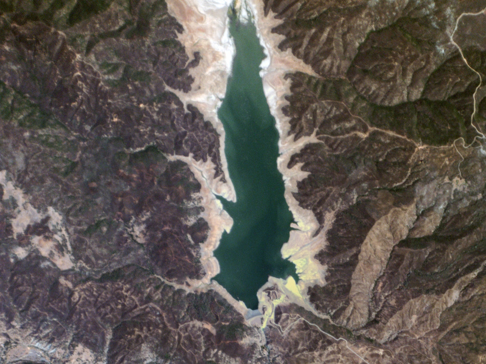 Click photo to download. Caption: A July 2014 Planet Labs satellite image of a reservoir in California's Lake County that supplies water to nearby Yolo County. In a non-drought year, according to Planet Labs, the visible water would cover roughly twice the area as it does in this picture. Credit: Planet Labs via Wikimedia Commons.