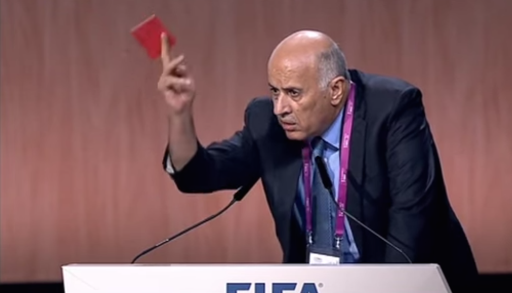Click photo to download. Caption: Palestinian soccer official Jibril Rajoub waives a symbolic red penalty card at Israel during the 65th FIFA Congress. Credit: YouTube.