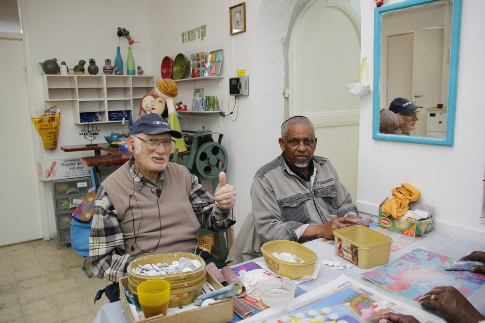 "Click photo to download. Caption: The senior citizen ""artisans"" at Lifeline for the Old in Jerusalem, pictured alongside their workshop materials. Credit: Bonnie Geller/Lifeline for the Old."