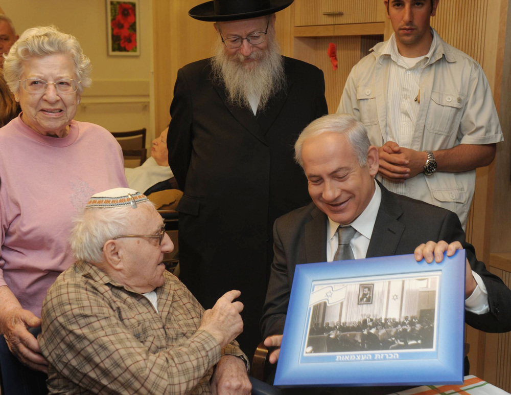 Click photo to download. Caption: In April 2012, Israeli Prime Minister Benjamin Netanyahu visits senior citizens living at a retirement home in Jerusalem, showing them a picture of David Ben-Gurion's announcement of Israeli independence at Tel Aviv's Independence Hall on May 14, 1948. Credit: Amos Ben Gershom/GPO/Flash90.