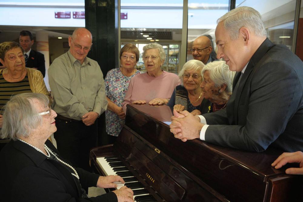 Click photo to download. Caption: Israeli Prime Minister Benjamin Netanyahu (right) visits senior citizens living at a retirement home in Jerusalem on April 17, 2012. Credit: Amos Ben Gershom/GPO/Flash90.
