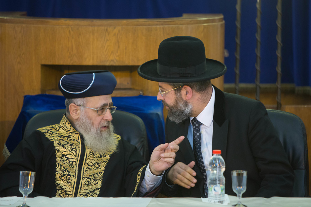 Click photo to download. Caption: Sephardic Chief Rabbi of Israel Yitzchak Yosef (left) and Ashkenazi Chief Rabbi of Israel David Lau (right) speak at a rabbinic ordination ceremony of the Israeli Chief Rabbinate in Jerusalem on Sept. 4, 2014. Yosef recently issued a call to action for the Sephardic Jewish community to join Ashkenazim in embracing pre-marriage genetic testing. Credit: Yonatan Sindel/Flash90.