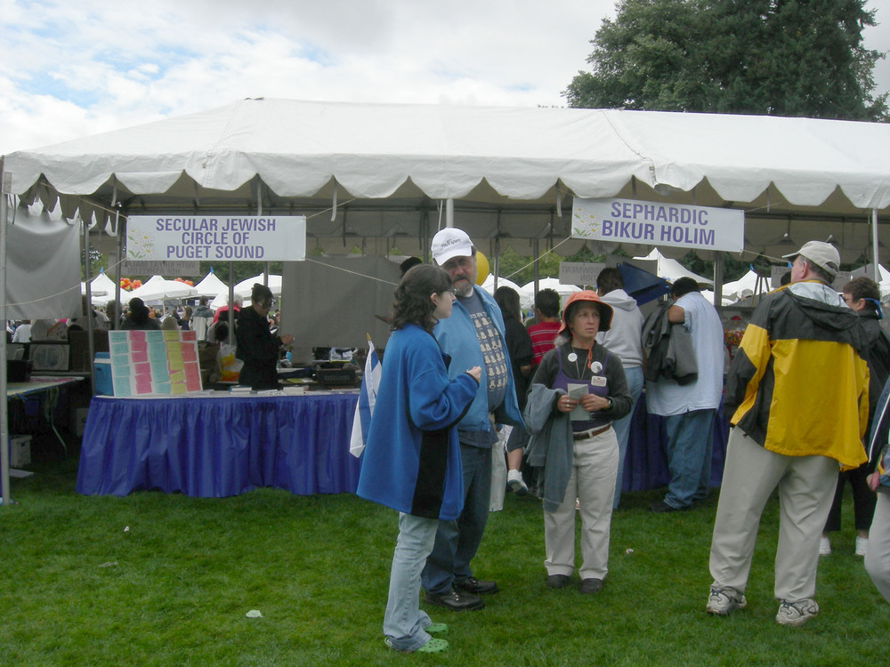 """Click photo to download. Caption: The Jewish Community Festival in Bellevue, Wash., in August 2007. At left is the booth of the Secular Jewish Circle of Puget Sound, which brings people together """"to celebrate Jewish culture and heritage in a non-religious setting."""" Surveys on American Judaism by institutes such as the Pew Research Center often ignite debates on religious vs. secular Jewish observance and identification. Credit: Joe Mabel via Wikimedia Commons."""