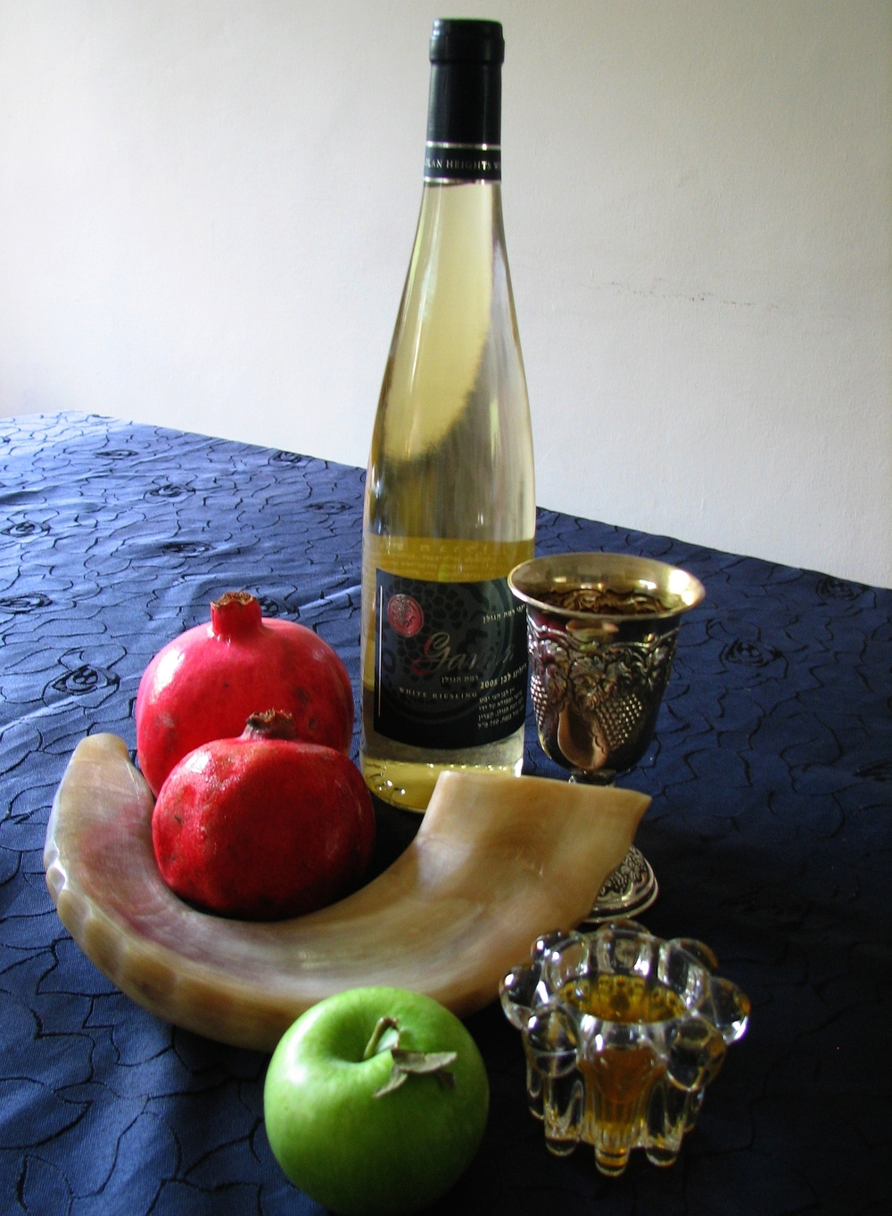 Click photo to download. Caption: Symbols of Rosh Hashanah, the Jewish New Year, including the shofar, an apple and honey, pomegranates, wine, and a silver Kiddush cup. Credit: Gilabrand via Wikimedia Commons.