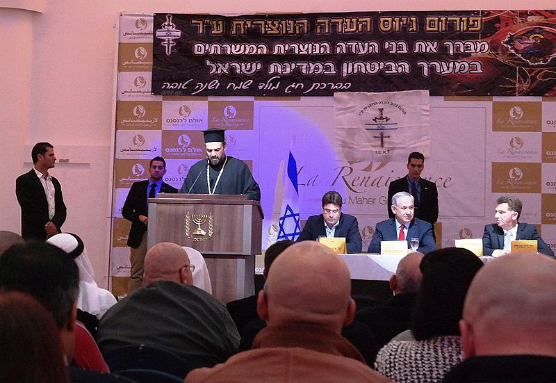 Father Gabriel Naddaf addresses Christian IDF soldiers in December 2014, with Israeli Prime Minister Benjamin Netanyahu (sitting at table in center) in attendance. Credit: Maor X via Wikimedia Commons.