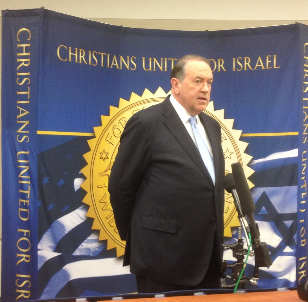 Click photo to download. Caption: On Monday, Republican presidential candidate and former Arkansas governor Mike Huckabee speaks to reporters at the Christians United for Israel Washington Summit. Credit: Jacob Kamaras.