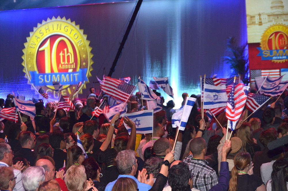 Click photo to download. Caption: Attendees of the 10th Christians United for Israel Washington Summit wave Israeli and American flags on Monday night. The next morning brought an announcement of a nuclear deal between Iran and world powers. Credit: Maxine Dovere.